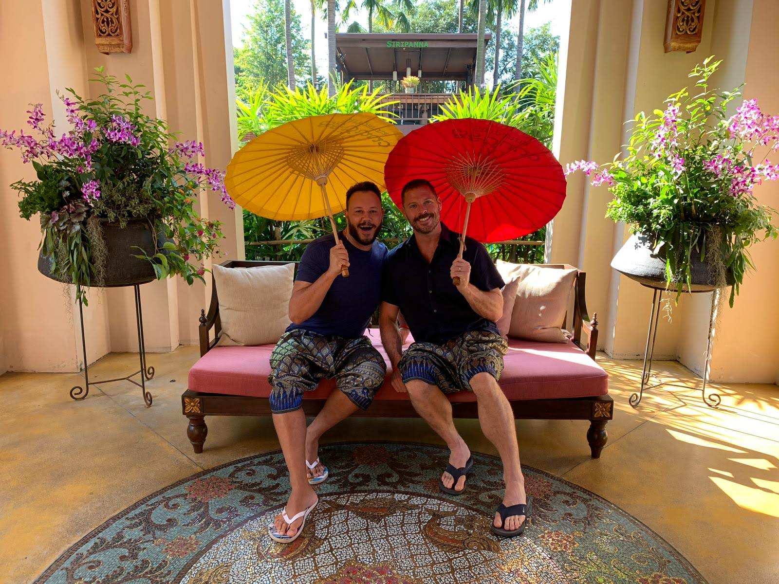 Two gay travellers in Thailand wearing traditional clothes and holding umbrellas.
