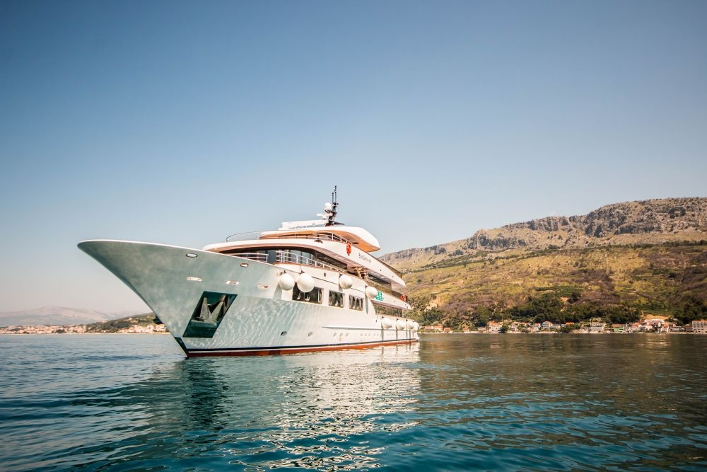 A beautiful image of The Black Swan docked near a Croatian island.