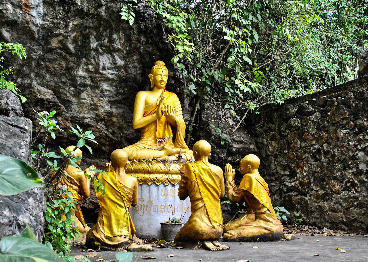 Four monk statues praying to a Buddhist Statue in Cambodia.
