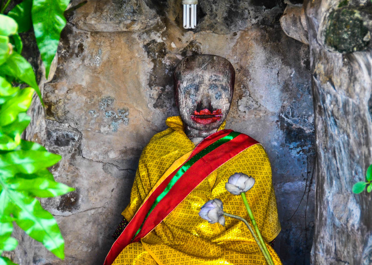 An ancient Cambodian wood statue is wrapped in marigold robes and decorated with lipstick.