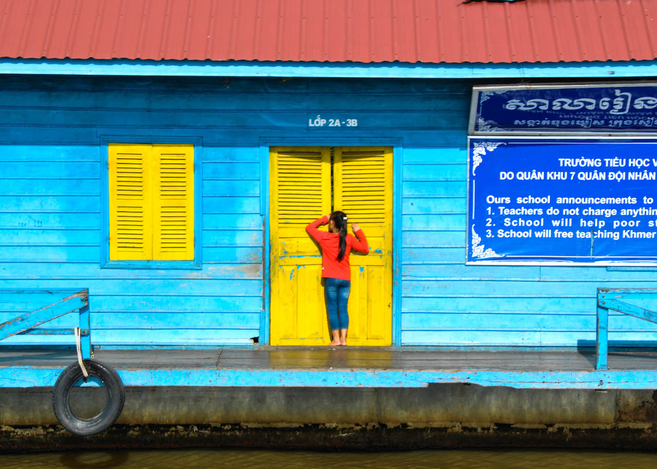 A Cambodian girl peeks into a brightly coloured school on the bank of the Mekong River.