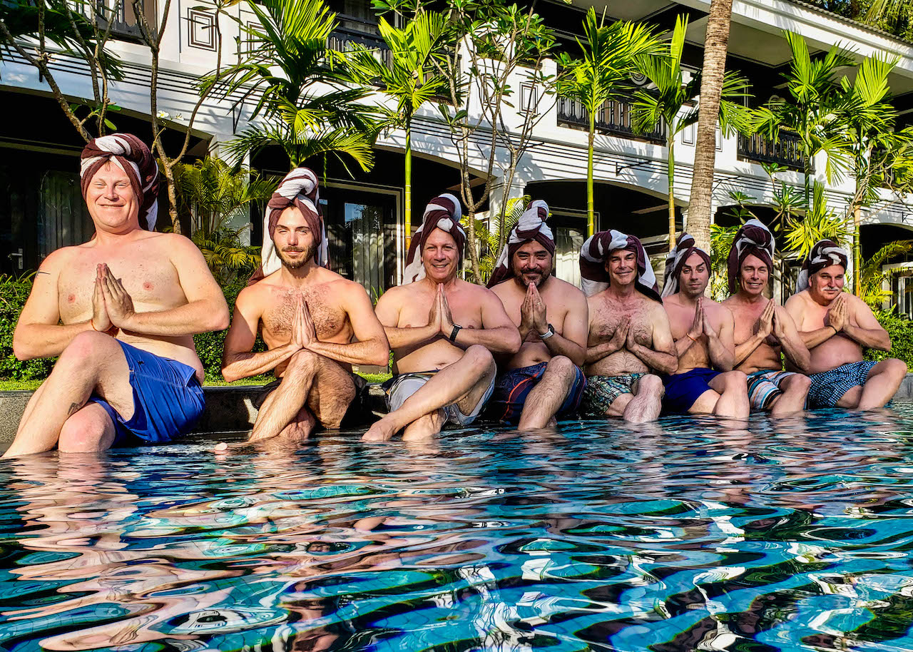 Out Adventures' 2018 Cambodia and Laos gay tour group posing with towel headdresses at the hotel pool.