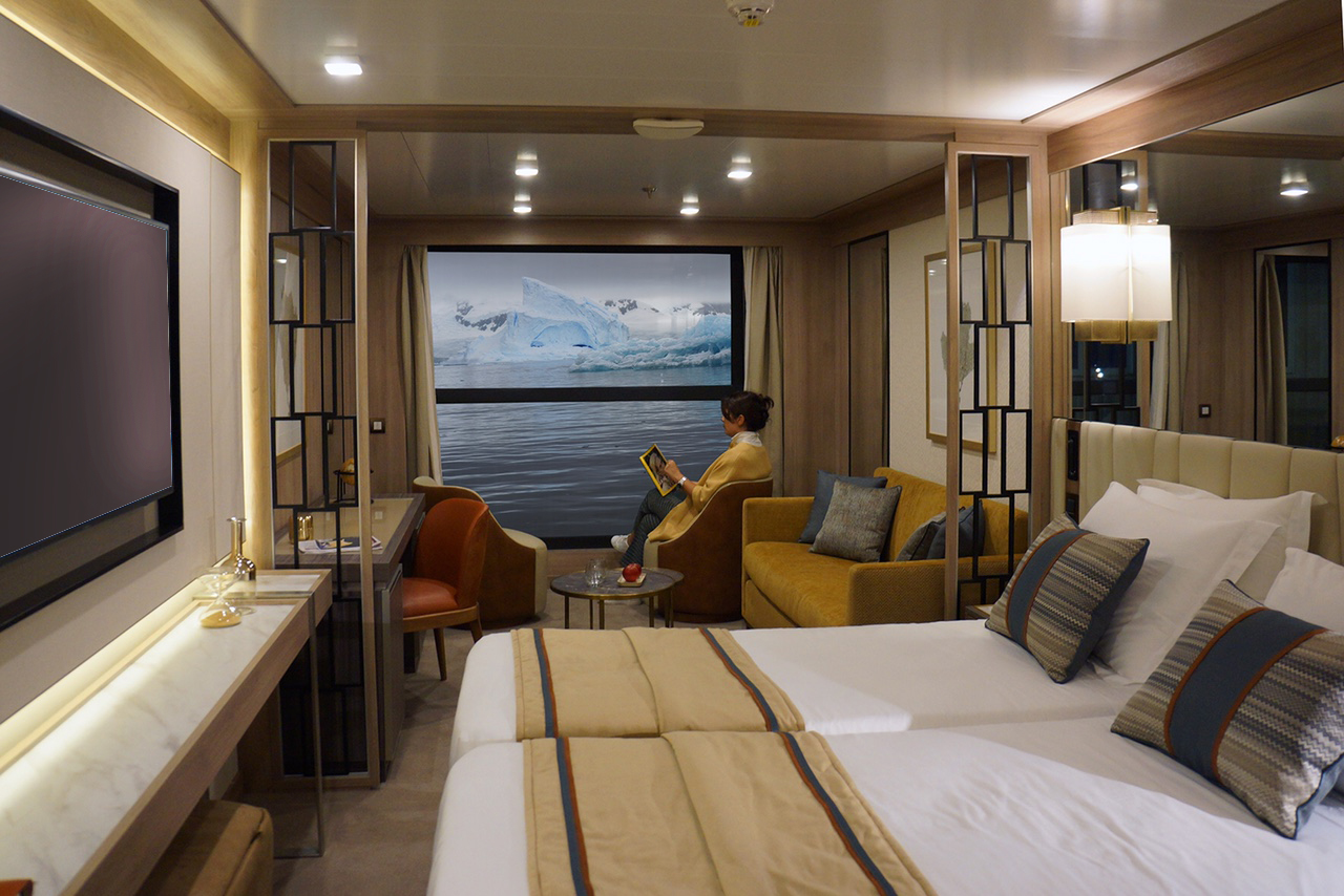 A passenger kicking back in The World Explorer's Infinity Suite.