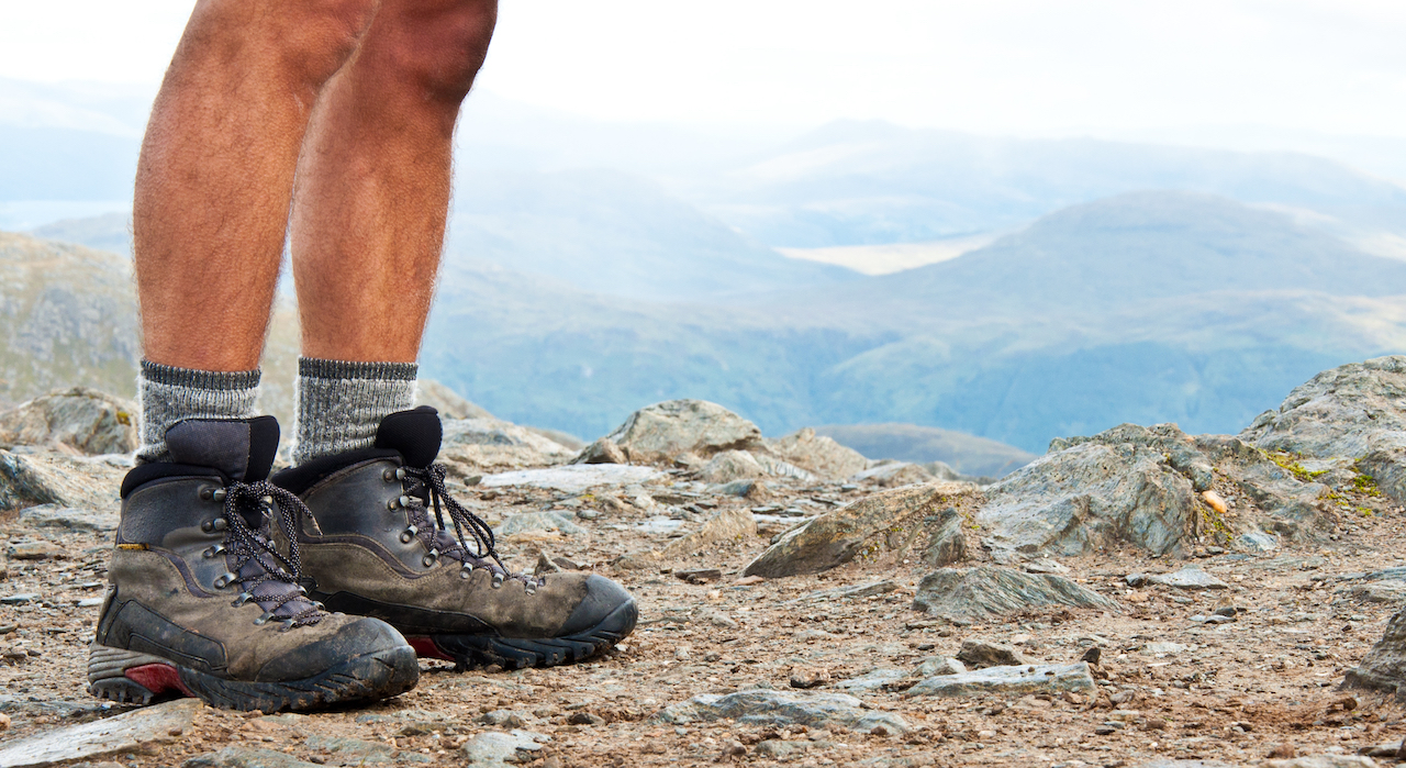 A photo of a man's calfs and hiking boots while standing above an epic fjord.