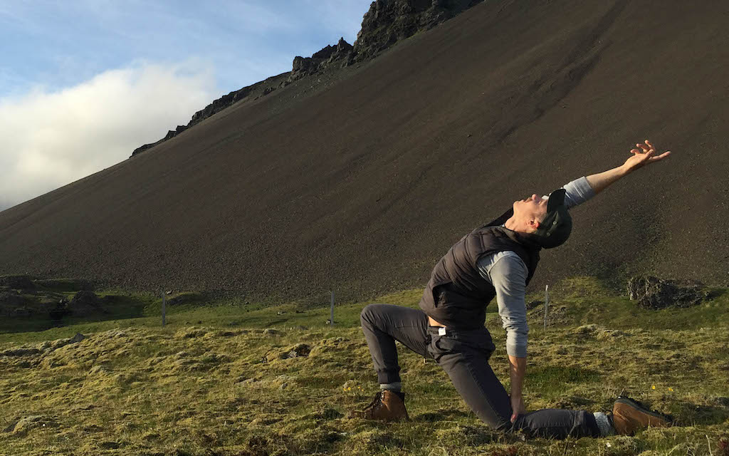 Adam Bolton enjoys a deep lunge during a gay yoga retreat with a hilly landscape in the background.