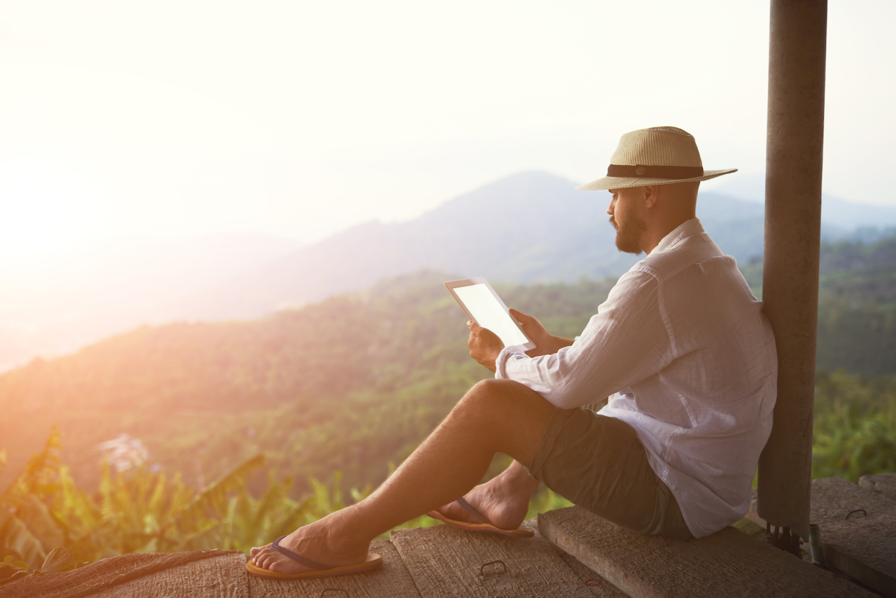 A gay man sits alone during a yoga retreat to read.