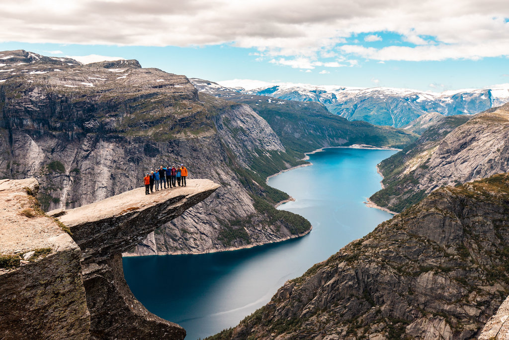 A group of gay hikers pose together on the ogerly Trolltunga peak above an epic fjord.