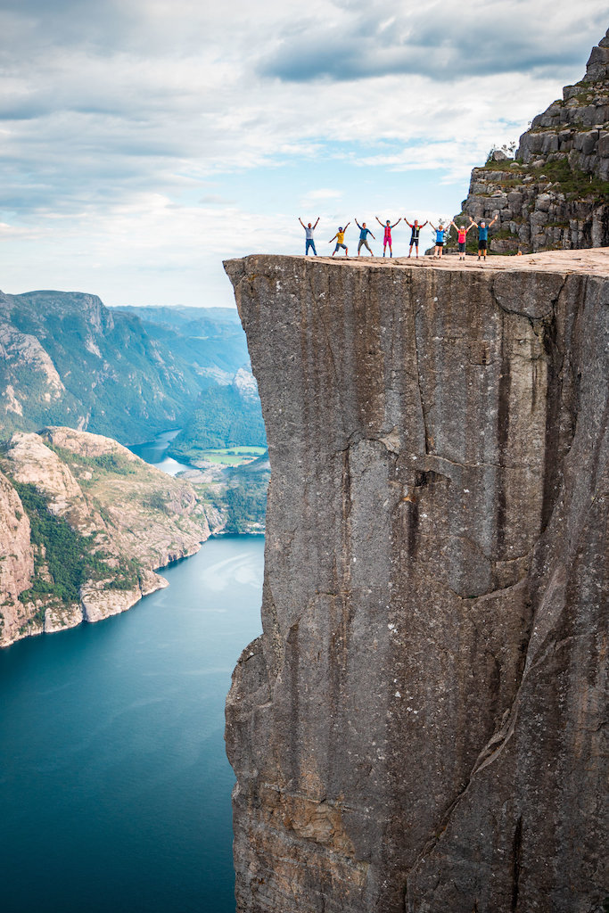 A group of gay hikes jump and pose on top of the death-defying Preikestolen.