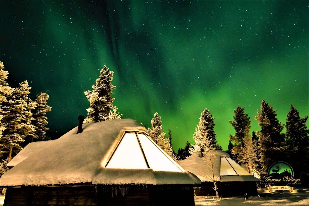 The Northern Lights dancing above the glass-roofed cabins featured on Out Adventures' gay Finland tour.