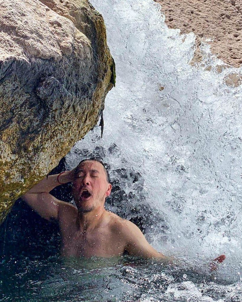 """A gay traveller """"showering"""" under a small waterfall in a Chilean hot spring."""