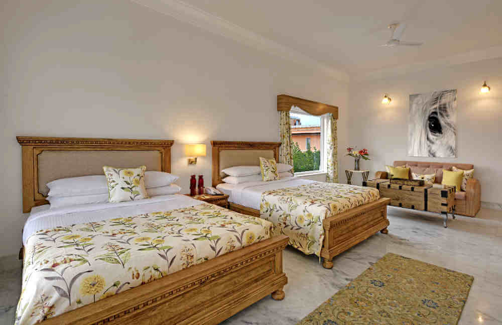 An example of a Heritage Chamber room outfitted with two twin beds at the Fate Garh in Udaipur.