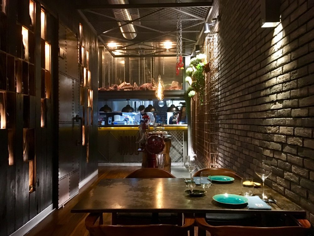 Iron and brick walls as well as signature spotlights define MUU Steakhouse's interior design.