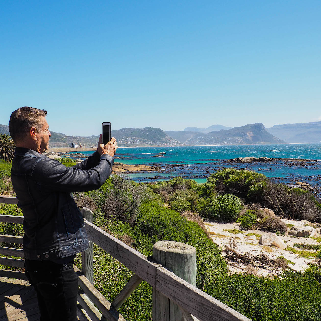 A gay traveller takes a photo of the Cape of Good Hope.
