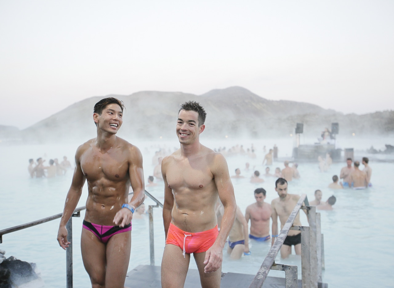 Two gay travellers in speedos coming out of Iceland's Blue Lagoon.