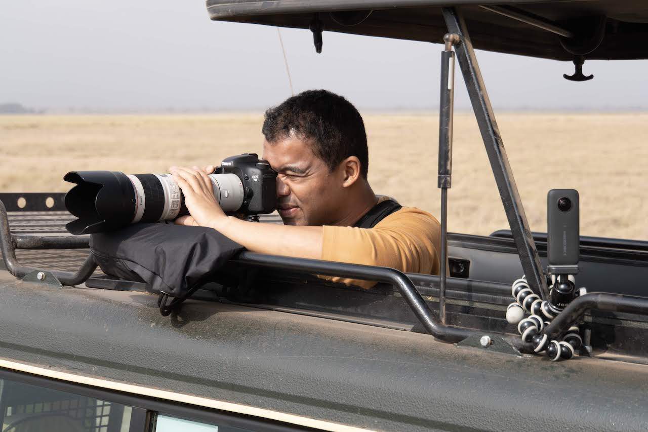 A photographer steadies his lens as he attempts to shoot a distant, unseen animal in the Masai Mara.