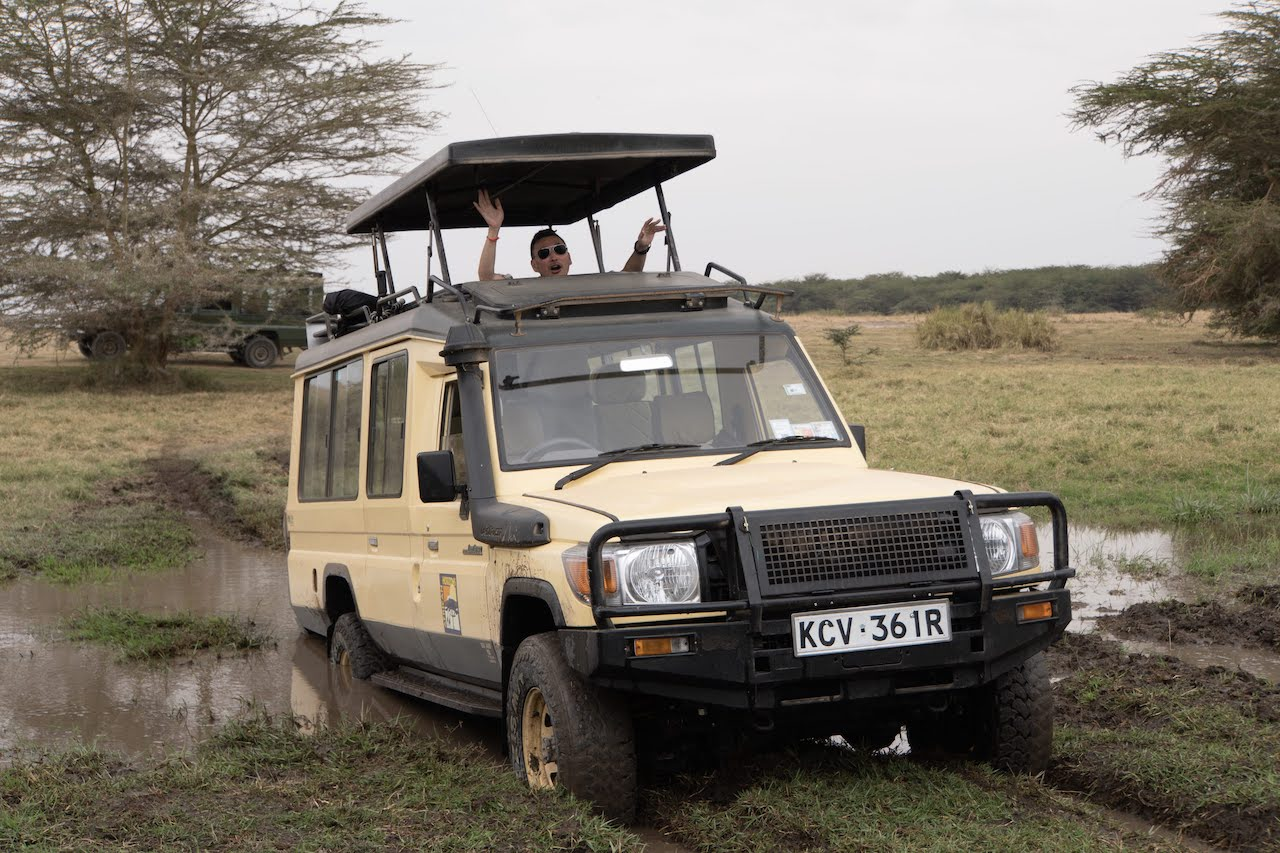 A traveller laughs as his safari vehicle gets stuck in a mud pit.