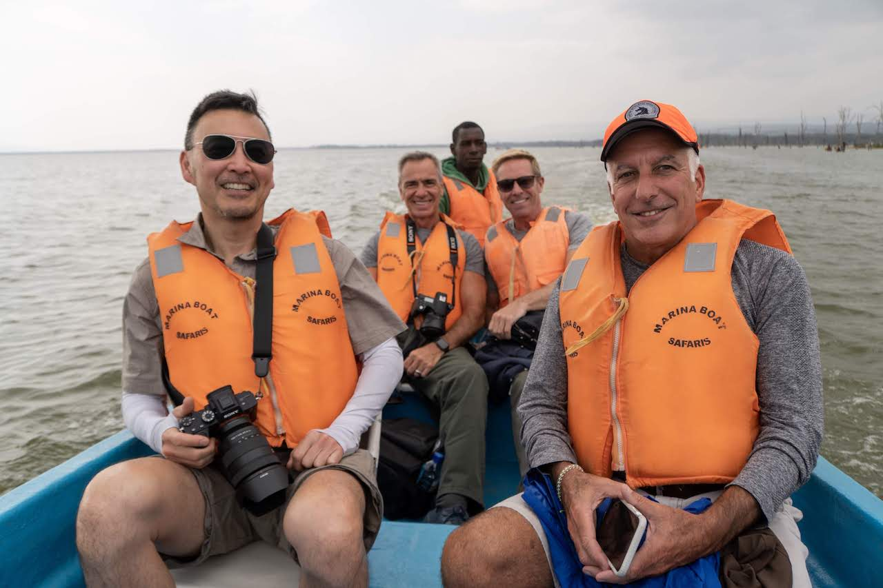 A group of travellers wearing life jackets aboard a boat on Lake Nakuru.
