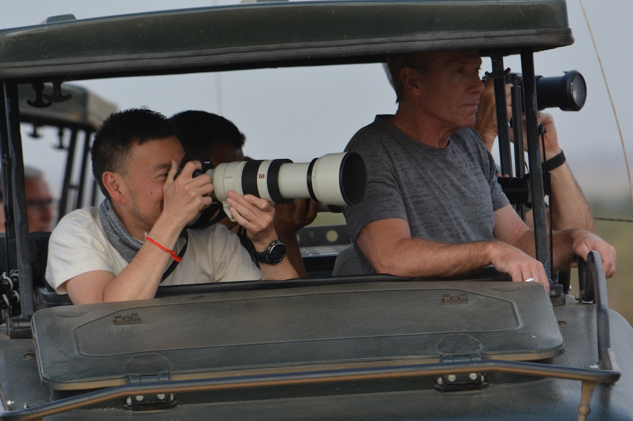 Travellers photograph wildlife in Africa.