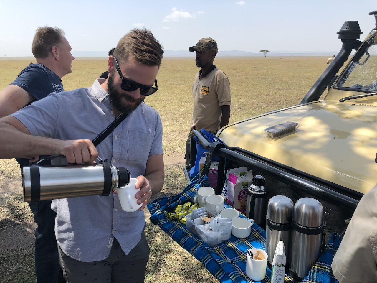 Robert Sharp, Founder of Out Adventures, pours coffee between game drives in Kenya.