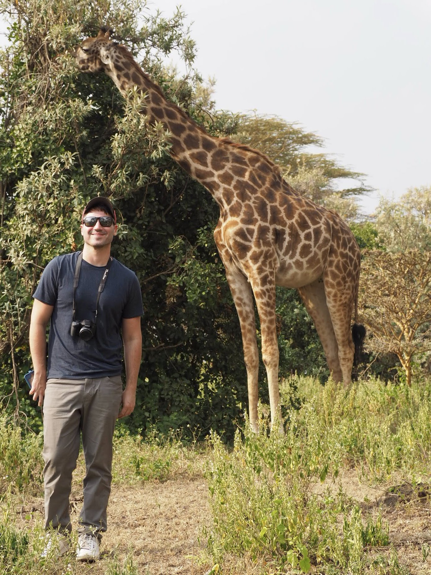 A gay traveller poses in front of a giraffe on Crescent Island.