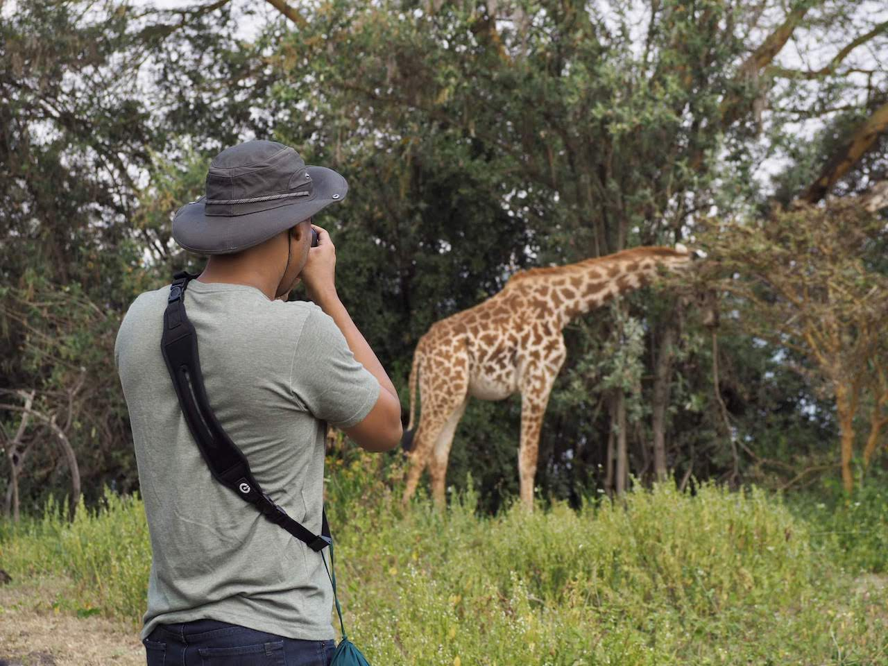 One traveller photographs a giraffe in the distance on Crescent Island.