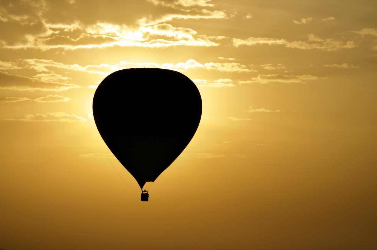 A lone hot air ballon is backlit by the morning sun in Kenya.