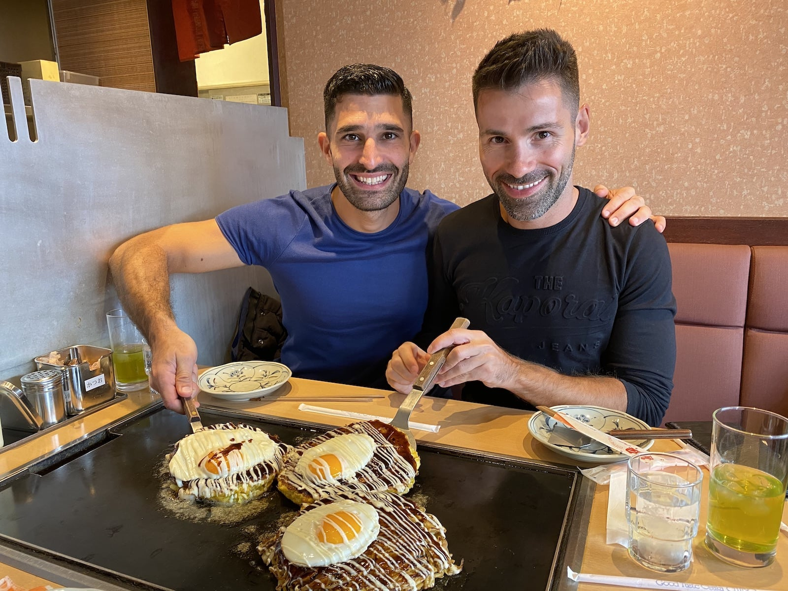 Two gay men enjoying a fried Japanese pancake.