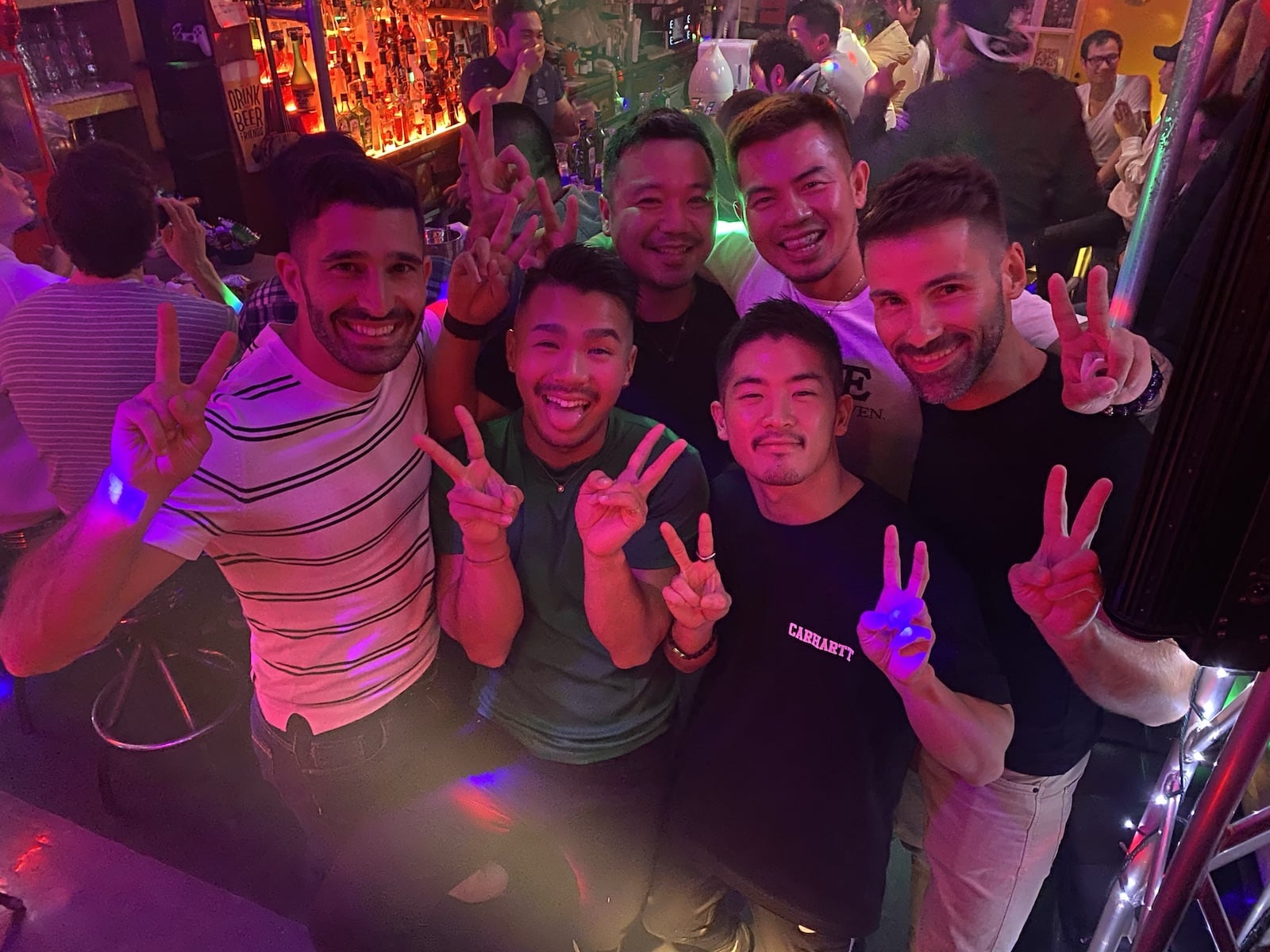 Nomadic Boys posing with a small crew of gay Japanese locals at a night club while exploring Tokyo's Shinjuku's Ni-Chōme neighbourhood.