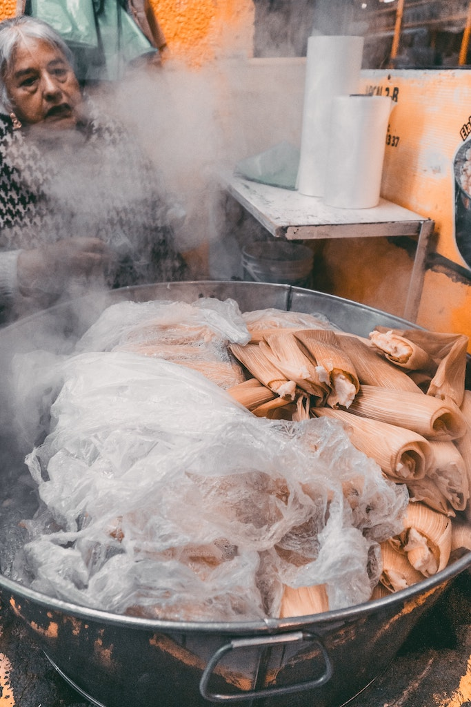 A tamale vendor steaming her masa in corn husks.