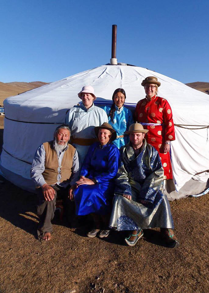 Travellers wear traditional Mongolian clothing and pose for a photo infront of a ger.