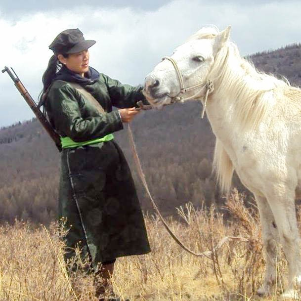 Out Adventures' local gay-welcoming Mongolia guide, Tuul, in the countryside with her horse.