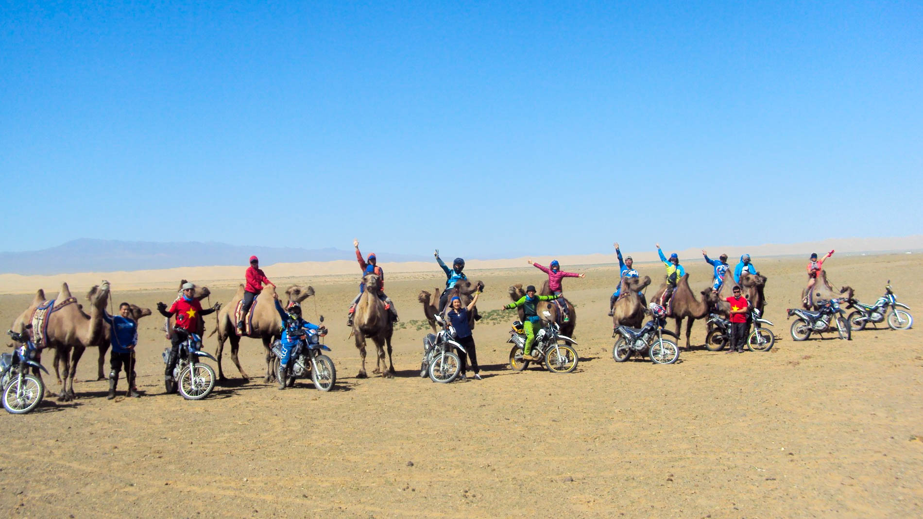 A group of travellers in Mongolia's Gobi Desert wave at the camera. Some are on camels while others are on motorcycles.