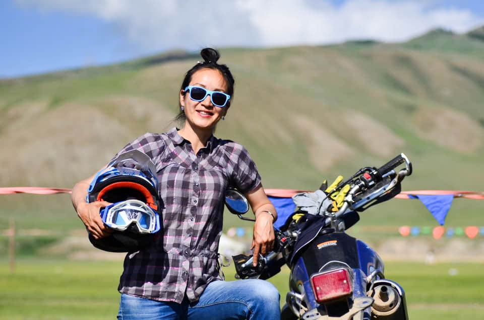 Out Adventures' local Mongolia guide posing with a motorcycle in the countryside.