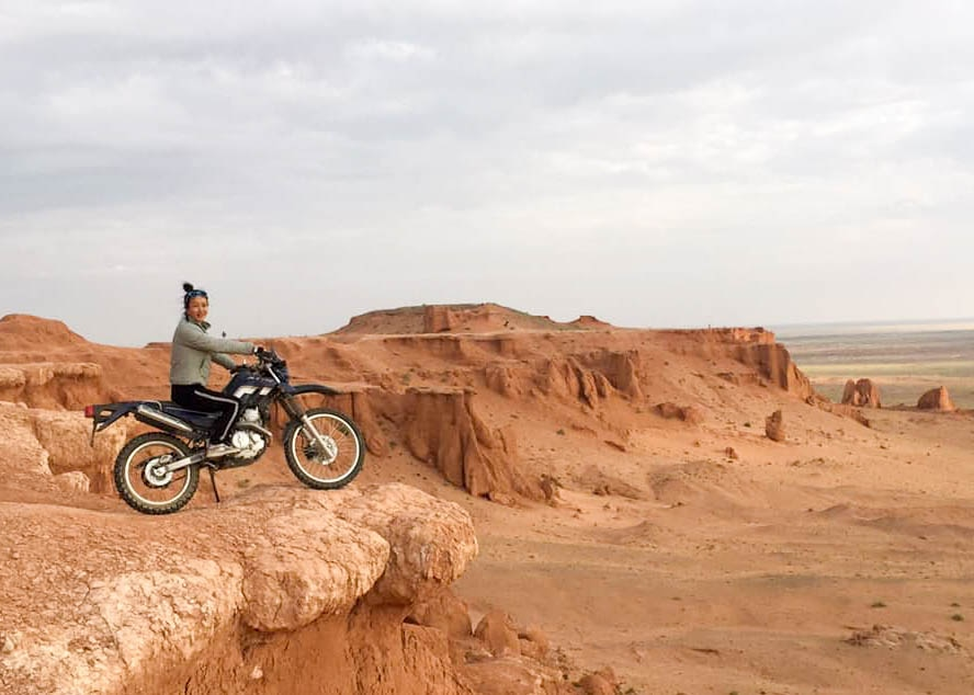 A local Mongolian riding a motorcycle in the Gobi Desert.