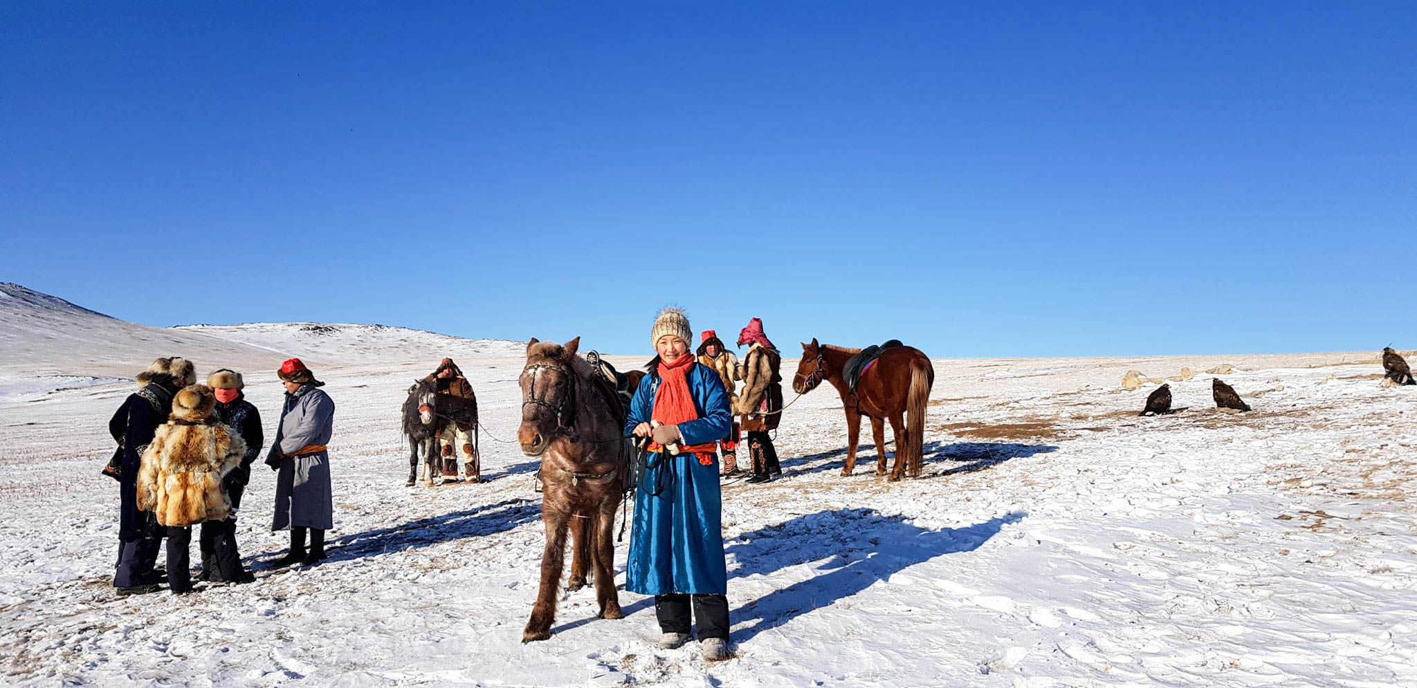 A snowy phjoto of Mongolia with locals and horses preparing to ride.