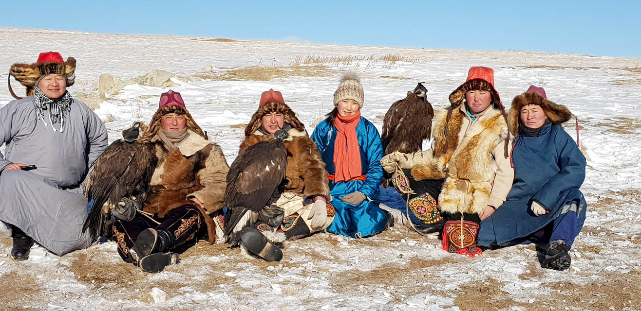 A group of Mongolians sit in the countryside with their pet golden eagles.