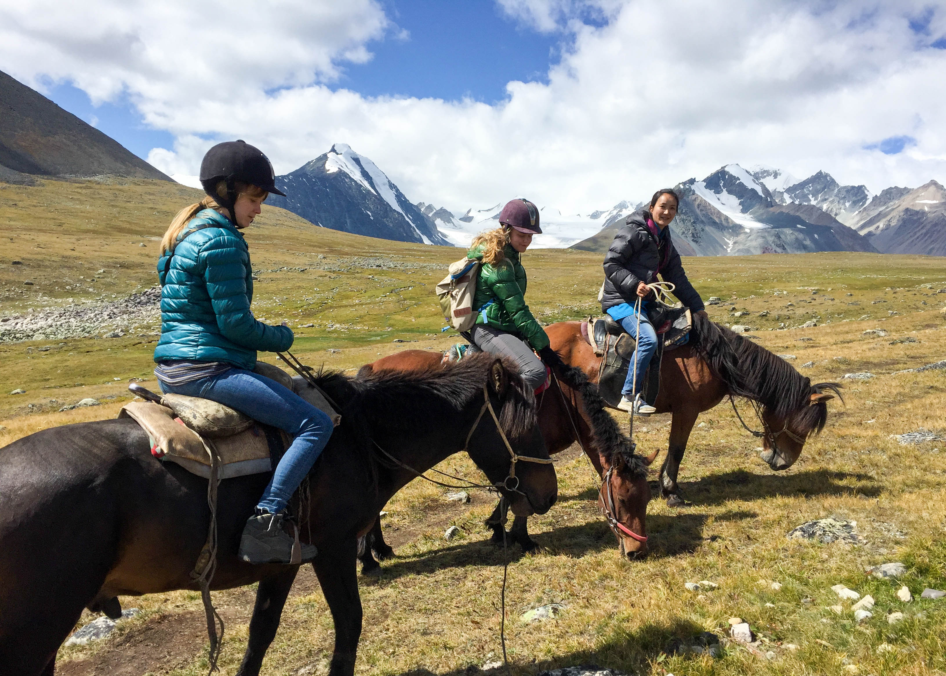 Our local female Mongolia guide on horseback leading two tourists.