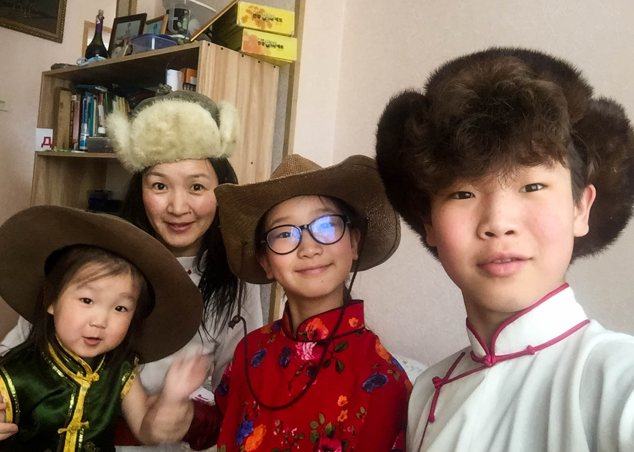 Our local Mongolia guide Tuul with three of her children all wearing different hats.