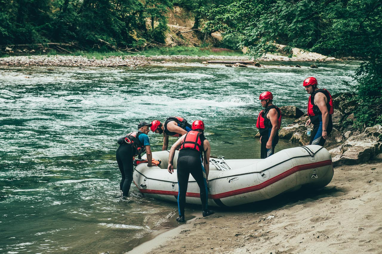 Travellers carrying a raft into the Tara River in Montenegro on a gay tour with Out Adventures..