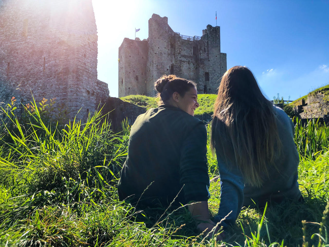 Devin and Jade sit in the grass below a medieval ruin on a sunny day.