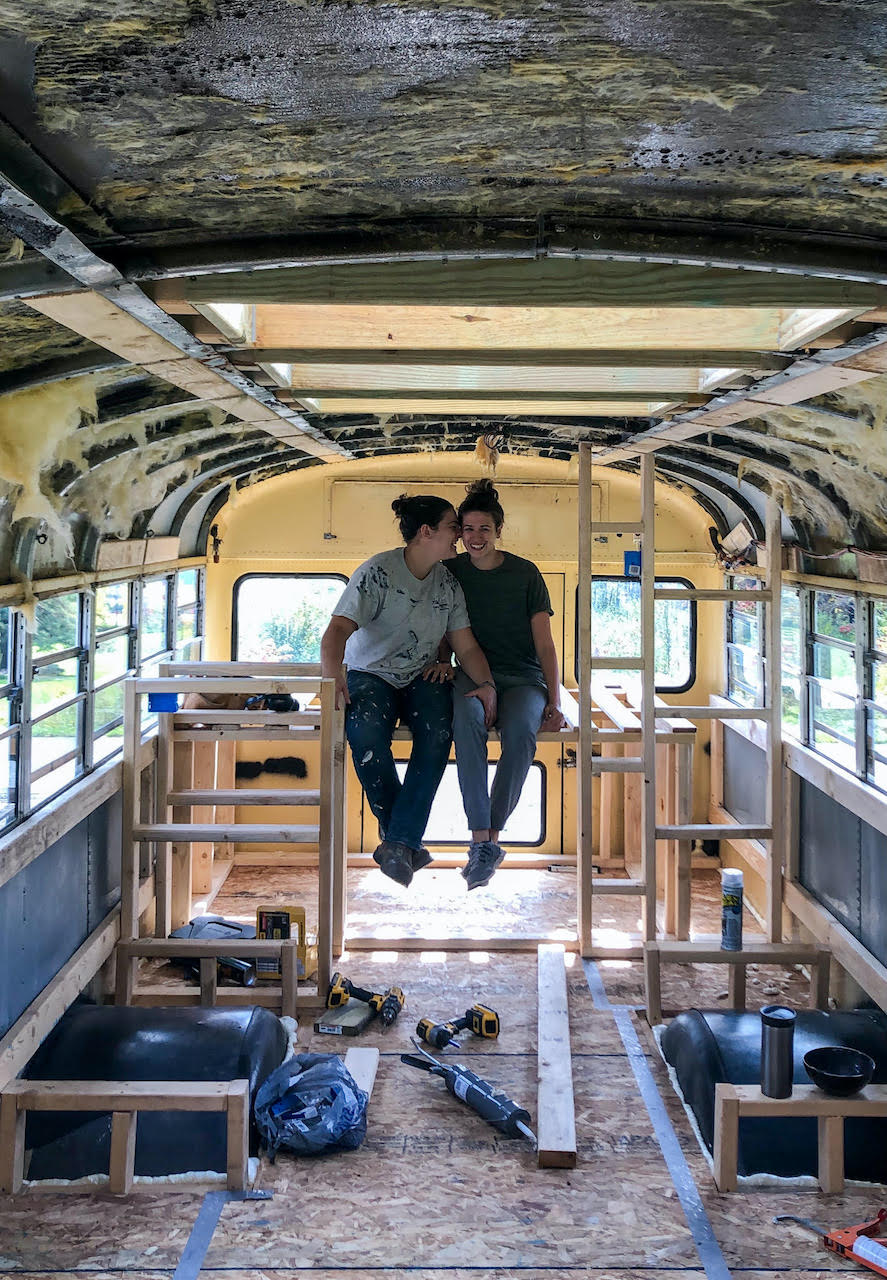Devin and Jade sit inside their half-finished tiny bus nuzzling.