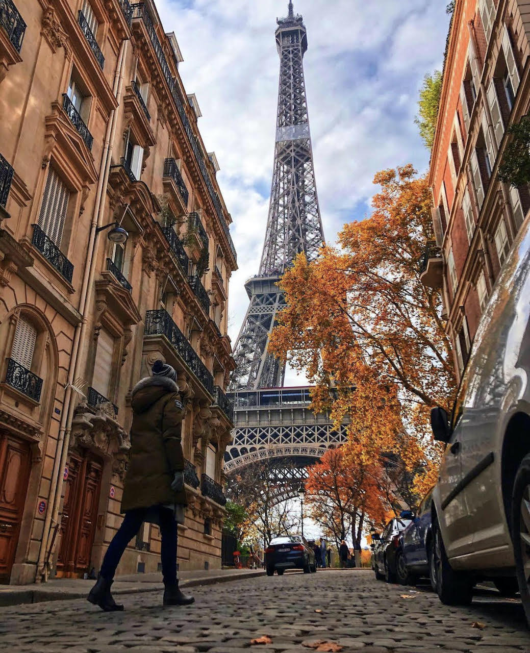 Devin Bonner—Out Adventures' lesbian Travel Specialist—walking towards the Eiffel Tower in autumn..