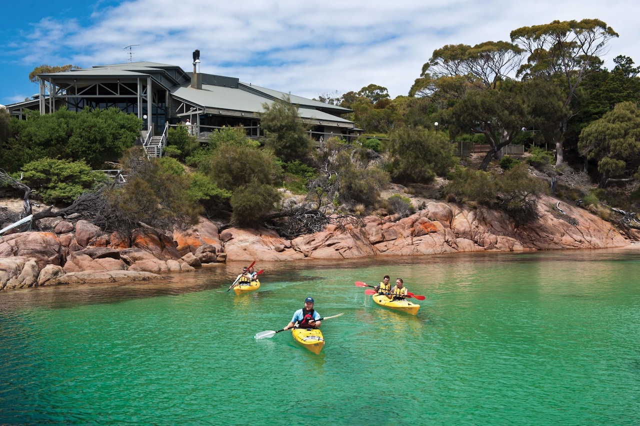 Three kayakers paddle out from Freycinet Lodge on Richardson's Beach.