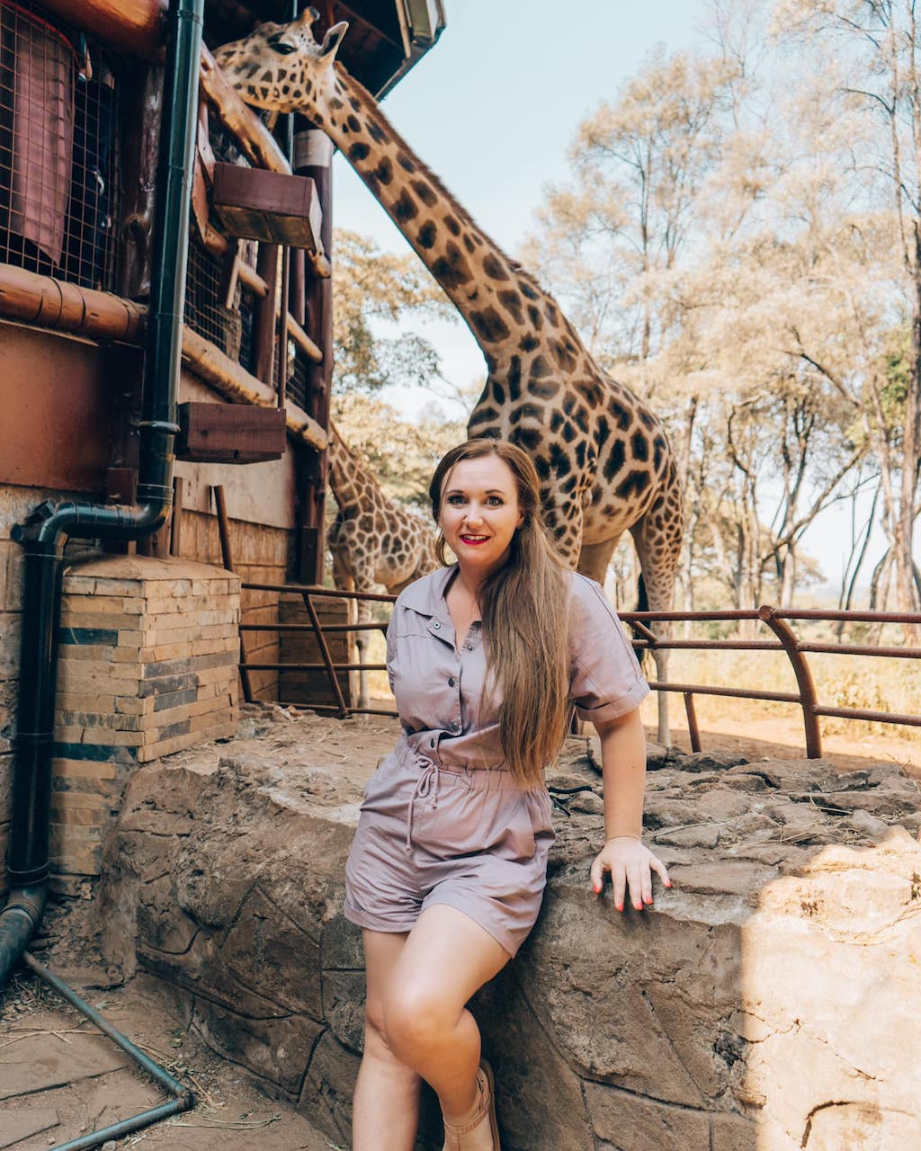 Meg poses for a picture in front of a giraffe at a sanctuary in Tanzania.