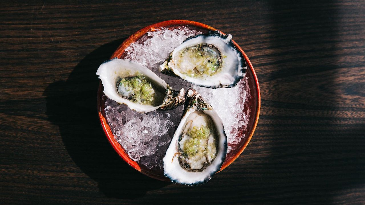 An aerial photo of three oysters sitting on a plate of ice at Lord Lygon Wine Shop.