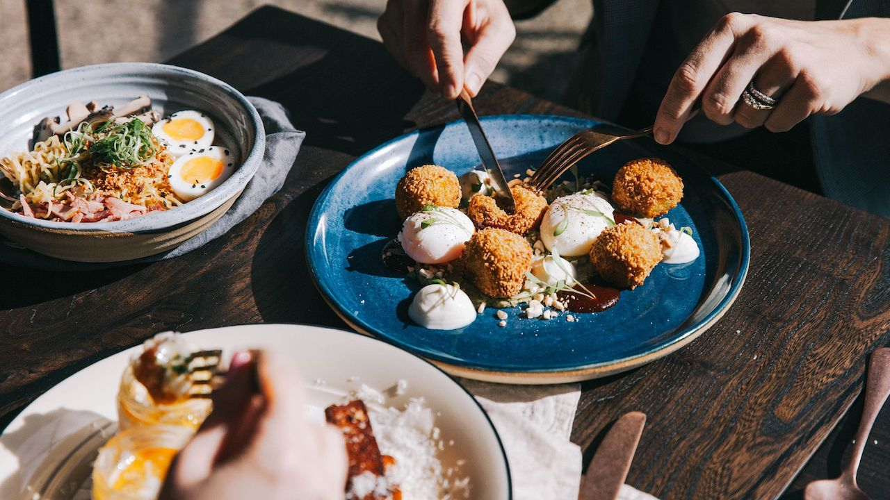 A traveller starts to dig into a beautiful dish at 1851 Coffee + Kitchen.
